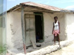 Beautiful strong sista in front of adobe house in Meillac, Haiti