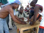 Brothers paying dominoes at a camp in Taba, Port-Au-Prince